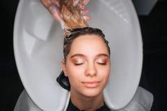 Odgórny widok piękna młoda kobieta ono uśmiecha się z zamkniętymi oczami podczas gdy fryzjer blondynki płuczkowy włosy Włosiana o obrazy royalty free