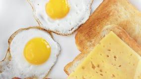 Odgórnego widoku apetyczny posiłek smażył jajko z grzanka bekonem na talerzu w górę obracanie strzału i serem zbiory wideo
