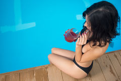 Odgórnego widoku brunetki kobiety obsiadanie blisko pływackiego basenu i pić koktajlu na tle perfect aqua Obraz Royalty Free