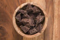 Odgórnego widoku ciemni czekoladowi kawały w drewnianym pucharze na stole Obraz Stock