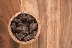 Odgórnego widoku ciemni czekoladowi kawały w drewnianym pucharze na stole Zdjęcia Stock