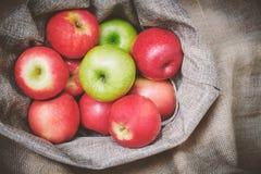 Odgórnego widoku czerwoni jabłka, zieleni jabłka w kosz pokrywie z brown sukienną tło teksturą zdjęcie stock
