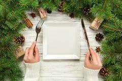 Odgórnego widoku dziewczyny chwyty rozwidlają i są gotowi jeść nóż w ręce Opróżnia białego kwadrata talerza na drewnianym bożego  zdjęcie stock