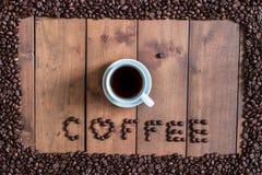 Odgórnego widoku filiżanka kawy z kawowych fasoli kwadrata ramą na drewnianym Zdjęcie Royalty Free