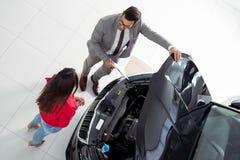 Odgórnego widoku fotografia młody męski konsultant i nabywcy podpisuje kontrakt dla nowego samochodu obraz royalty free
