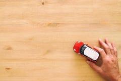odgórnego widoku fotografia man& x27; s ręki mienia zabawki samochód nad drewnianym tłem zdjęcia stock