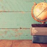 Odgórnego widoku fotografia rocznik kula ziemska i sterta książki na drewnianym biurku rocznik filtrujący wizerunek zdjęcia royalty free