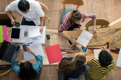 Odgórnego widoku grupa nastoletni przyjaciele być ruchliwie działaniem w drużynie z raportami i laptopie przy uniwersytetem zdjęcia royalty free