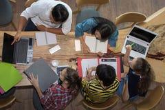 Odgórnego widoku grupa nastoletni przyjaciele pracuje w drużynie z raportami i laptopem obrazy royalty free