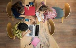 Odgórnego widoku grupa nastoletni przyjaciele pracuje w drużynie z raportami na drewnianym stole i laptopie obrazy stock