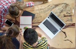 Odgórnego widoku grupa nastoletni przyjaciele pracuje w drużynie z raportami na drewnianym stole i laptopie zdjęcie royalty free