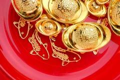 Odgórnego widoku grupa złoci ingots na czerwonej tacy z ryba wzorem C Obraz Stock