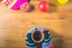 Odgórnego widoku kobiet ` s ręki, rękawiczki, Jedwabniczy kapelusz, barwione piłki i filiżanka kawy na drewno stole, Zdjęcia Stock