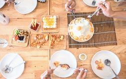 Odgórnego widoku ludzie jedzą posiłki Deserowych Przyjaciele i rodzina świętują z jedzeniem na drewnianym stole dla przyjęcia Zdjęcie Royalty Free