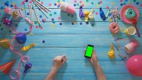 Odgórnego widoku mężczyzna planistyczny urodzinowy używa telefon komórkowy gestykuluje z zieleń ekranem zdjęcie wideo