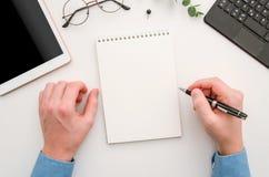Odgórnego widoku mężczyzny ręki z notepad na biurowym biurku Miejsce pracy z notatnikiem, pastylką, szkłami, piórem i szpilką, Mi obraz stock
