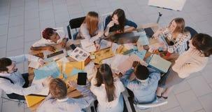 Odgórnego widoku młody szczęśliwy biznesowy kreatywnie drużynowy brainstorming przy biuro stołem, doświadczonej kobiety po zdjęcie wideo