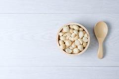 Odgórnego widoku macadamia skorupa w drewnianym pucharze i dokrętki Zdjęcia Stock