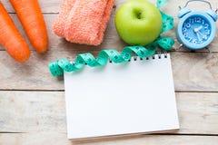 Odgórnego widoku marchewka z błękitnym stetoskopem, pomiarowa taśma, jabłko, budzik i notatnik na drewnie, zgłaszamy tło zdjęcia royalty free