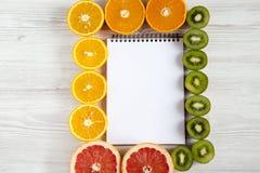 Odgórnego widoku mieszkania nieatutowy notatnik z pokrojonym kiwi, pomarańcze, grapefruitowym, i mandarynka na lekkim tle zdjęcie royalty free