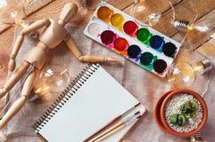 Odgórnego widoku mockup z notepad, maluje, muśnięcia, kwiat, drewniana atrapa i żarówka na, drewnie i tkaniny tle Obrazy Royalty Free