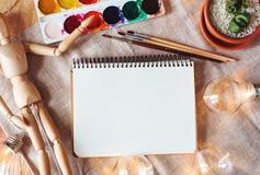 Odgórnego widoku mockup z notepad, maluje, muśnięcia, kwiat, drewniana atrapa i żarówka na, drewnie i tkaniny tle Fotografia Stock