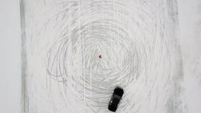 Odgórnego widoku obracanie strzelał ślizgowego i dryfującego czarnego sportowego samochód poruszającego na okrąg anteny strzale zbiory wideo