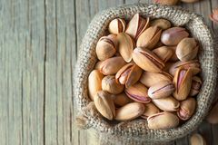 Odgórnego widoku pistacja w nutshell w burlap worku na drewnianym nieociosanym tle fotografia stock