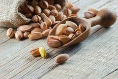 Odgórnego widoku pistacja w nutshell w burlap worku na drewnianym nieociosanym tle obrazy stock
