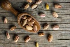 Odgórnego widoku pistacja w nutshell w drewnianej łopacie na drewnianym nieociosanym tle zdjęcie royalty free