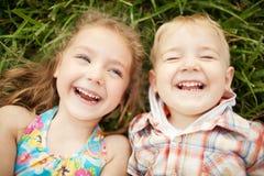 Odgórnego widoku portret dwa szczęśliwy ono uśmiecha się żartuje lying on the beach Fotografia Royalty Free