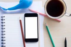 odgórnego widoku pusty ekran telefon komórkowy na notatniku i drewnianym des Obrazy Stock