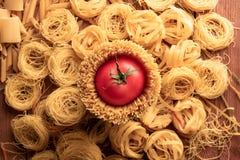 Odgórnego widoku różni typy makaron i geometryczny kształt z pomidorem obraz royalty free