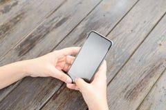 Odgórnego widoku ręka używać telefonu pustego ekran na drewnianym stole zdjęcie stock