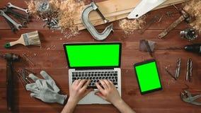 Odgórnego widoku rzemieślnika ręki pracuje przy laptopem i cyfrowym pastylki lying on the beach na stole z zieleń ekranem zdjęcie wideo