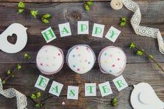 Odgórnego widoku skład Szczęśliwy Wielkanocny literowanie, gałąź z młodymi krótkopędami greenery, dekorował babeczki, biała barwi Fotografia Royalty Free