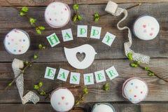 Odgórnego widoku skład Szczęśliwy Wielkanocny literowanie, gałąź z młodymi krótkopędami greenery, dekorował babeczki, biała barwi Obraz Stock