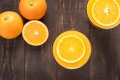 Odgórnego widoku sok pomarańczowy na drewnianym tle Zdjęcia Stock