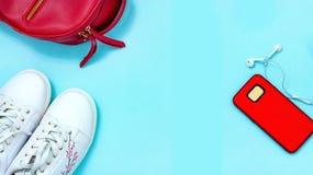 Odgórnego widoku sporta Przypadkowi ubrania ustawiają dla młodej kobiety Białych sneakers plecaka zegarka czerwony smartphone nad zdjęcia stock
