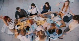 Odgórnego widoku szczęśliwa grupa ludzie biznesu pracuje wpólnie, łączący rękę, klascze odświętność sukces przy nowo zbiory wideo