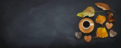 odgórnego widoku sztandar filiżanka nad blackboard tłem i suchymi jesień liśćmi zdjęcia royalty free