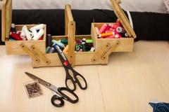 Odgórnego widoku Szwalne nici stubarwne w drewnianym pudełku na stole z dwa nożycami Zdjęcie Royalty Free