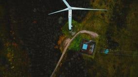 Odgórnego widoku trutnia latanie nad wiatraczka turbinowy działanie w bujny zieleni lesie, przyszłościowy alternatywny energii od zbiory wideo