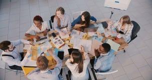 Odgórnego widoku ufny żeński lider zespołu wskazuje przy męskim pracownikiem przy biznesowego spotkania, pracy zespołowej i zbiory wideo