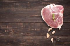 Odgórnego widoku wieprzowiny kotlecika surowy stek i czosnek, pieprz na drewnianym backgr Zdjęcia Stock