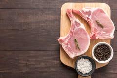 Odgórnego widoku wieprzowiny kotlecika surowy stek i czosnek, pieprz na drewnianym backgr Obrazy Royalty Free