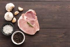Odgórnego widoku wieprzowiny kotlecika surowy stek i czosnek, pieprz, sól na drewnianym Zdjęcie Royalty Free