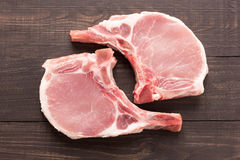 Odgórnego widoku wieprzowiny kotlecika surowy stek na drewnianym tle Zdjęcie Royalty Free