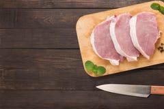 Odgórnego widoku wieprzowiny kotlecika surowy stek na tnącej desce i nóż na woode fotografia stock