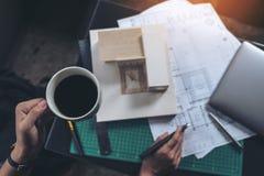 Odgórnego widoku wizerunek architekci myśleć masa modela i projektuje podczas gdy pijący gorącą kawę z sklepowym rysunkowym papie Fotografia Royalty Free